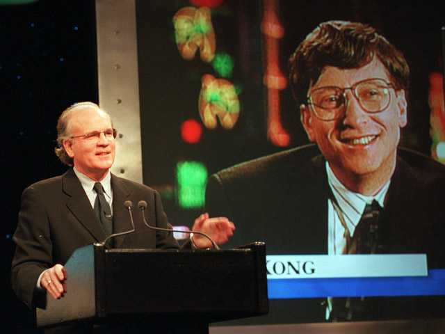 In this Dec. 14, 1995, photo, Robert Wright, president and chief executive officer of NBC, speaks in New York with Microsoft Chairman Bill Gates, displayed on screen, speaks from Hong Kong, during a news conference announcing that NBC and Microsoft would form a joint venture to start a cable news channel and related online service called MSNBC.