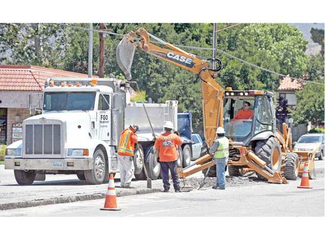 A crew performs road work along Newhall Avenue south of Valle Del Oro in Newhall on Monday.