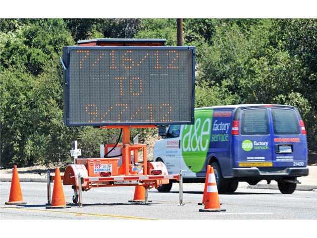 Traffic flows past a sign Monday warning of road work being conducted along Newhall Avenue south of Railroad Avenue in Newhall.