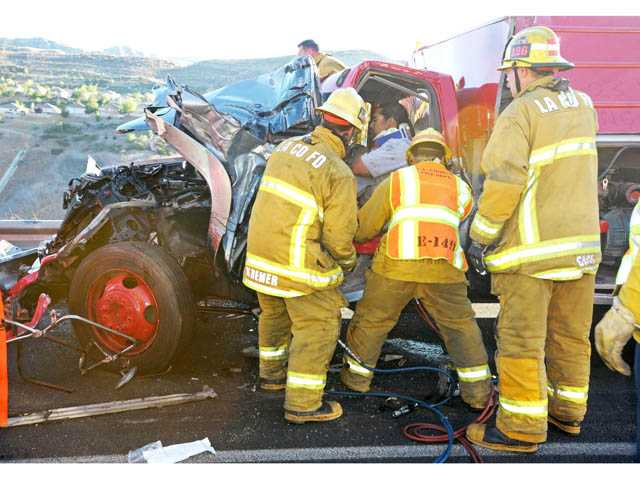 Firefighters work to free the driver of a pickup truck involved in a crash on southbound Interstate 5 north of Lake Hughes Road in Castaic on Monday.