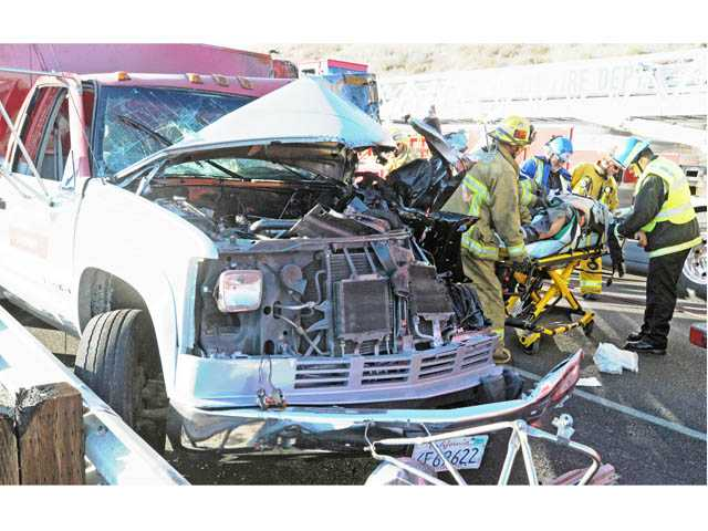 The front-end damage to the pickup truck is seen as firefighters and emergency medical technicians transport the truck's driver to an ambulance on southbound Interstate 5 north of Lake Hughes Road on Monday.