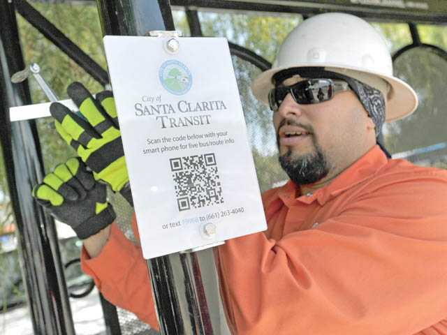 Street maintenance worker Robert Griego installs a sign with a QR code at a bus stop on Valencia Boulevard at Magic Mountain Parkway in Valencia on Tuesday.