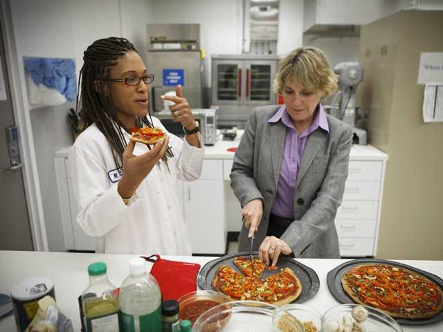 NASA's Advanced Food Technology Project manager Michele Perchonok, right, and Lockeed Martin Sr. Research Scientist Maya Cooper, try a pizza recipe being tested in a kitchen at Johnson Space Center July 3 in Houston, Texas.