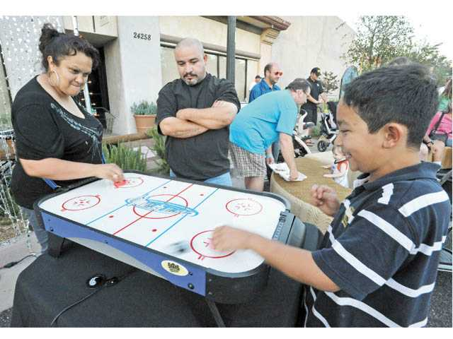Maria Herrera, left, and son Norrayaxan, 9, play on an air hockey table as husband Angel looks on at the June 21 Senses block party.