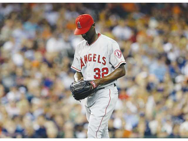 Los Angeles Angels relief pitcher LaTroy Hawkins walks to the dugout after giving up a two-run home run hit by Detroit Tiger Brennan Boesch in the seventh inning on Monday in Detroit.