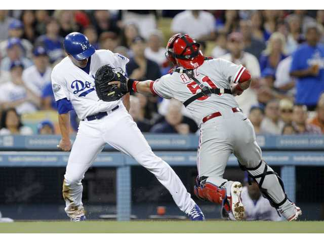 Philadelphia Phillies catcher Carlos Ruiz, right, tags out Los Angeles Dodger Mark Ellis on the third base line during the fourth inning on Monday in Los Angeles. The Phillies beat the Dodgers 3-2.
