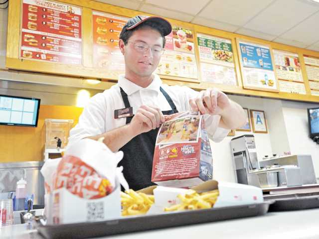 Recent Academy of the Canyons graduate Timothy Simon, 18, assembles orders behind the counter of Wendy's on Magic Mountain Parkway in Valencia on July 3.