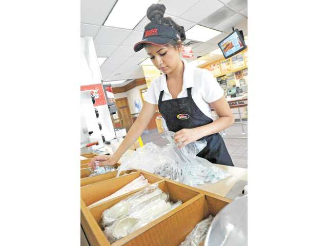 Canyon High student Paola Prado, 16, restocks condiments at Wendy's on Magic Mountain Parkway in Valencia on July 3.