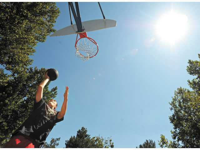 Nicolas Ratliff, 15, practices on the basketball court at Almendra Park in Valencia on Tuesday afternoon.