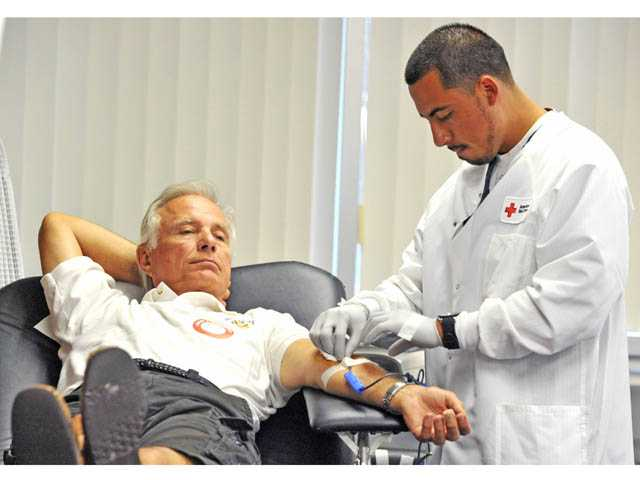 Phlebotomy technician Johnny Parada, right, checks on Peter Stamison, Sr., 69, of Stevenson Ranch, as he donates blood at the American Red Cross' blood drive at its Valencia office on Wednesday.