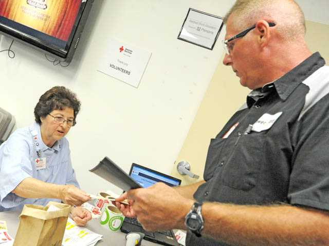 Volunteer Marie Ober, left, hands paperwork to Ron Leonhardt as he checks in for a blood donation