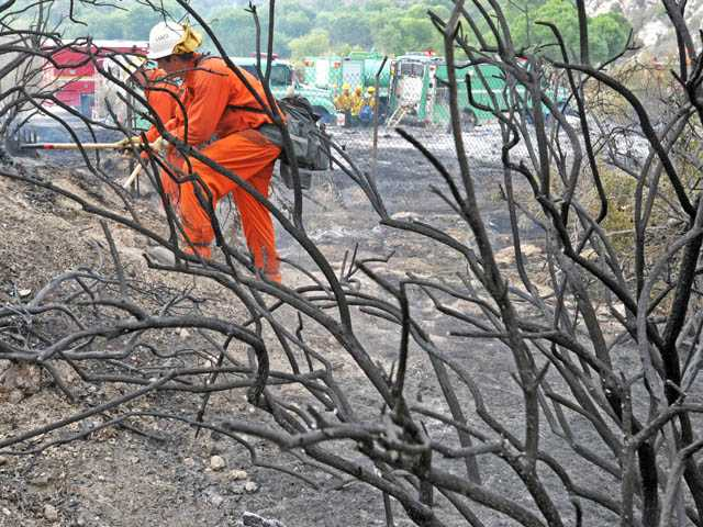 A hand crew mops up after a fire consumed brush along Soledad Canyon Road in Agua Dulce on Wednesday.