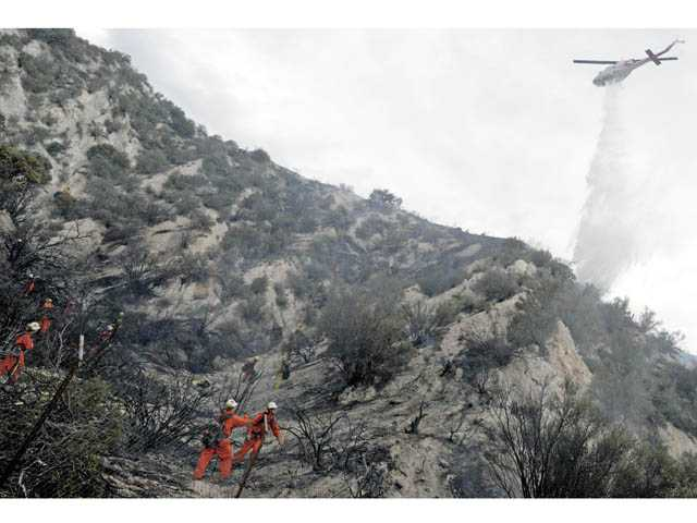 A helicopter makes a drop as firefighters mop up following a brush fire along Soledad Canyon Road in Agua Dulce on Wednesday.