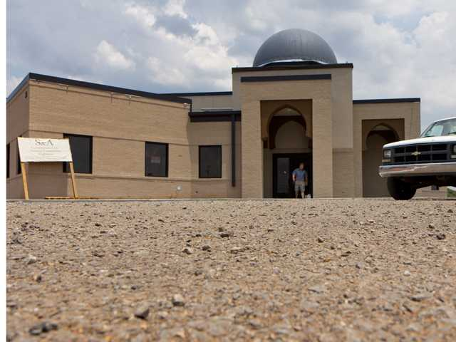 In a Thursday, June 21, 2012 file photo, a worker walks out of the construction site of a mosque being built in Murfreesboro, Tenn. The Islamic Center of Murfreesboro and its religious leader, Imam Ossama Bahloul, sued Rutherford County on Wednesday, July 18, 2012 and asked the federal court for an emergency order to let worshippers into the building before the holy month of Ramadan starts at sundown on Thursday. In May, a Rutherford County judge overturned the county's approval of the mosque construction and this month he ordered the county not to issue an occupancy permit for the 12,000-square-foot building. (AP Photo/Erik Schelzig, File)