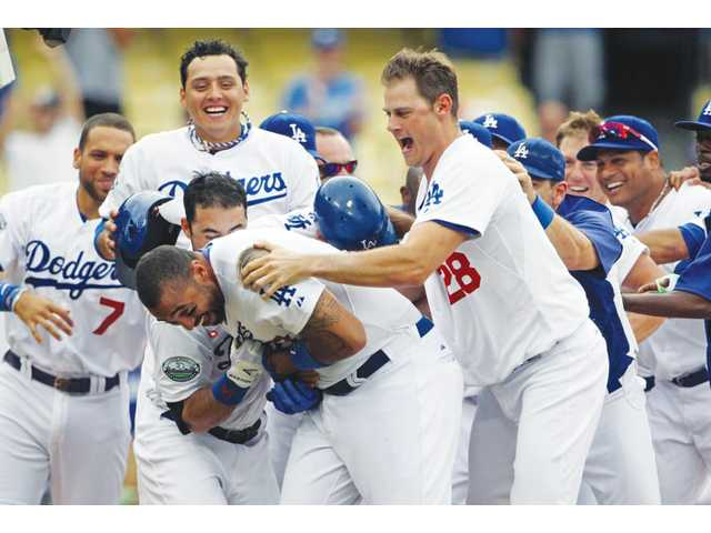 Los Angeles Dodgers outfielder Matt Kemp, center, is swarmed by teammates after hitting a walk-off home run against the Philadelphia Phillies on Wednesday in Los Angeles.