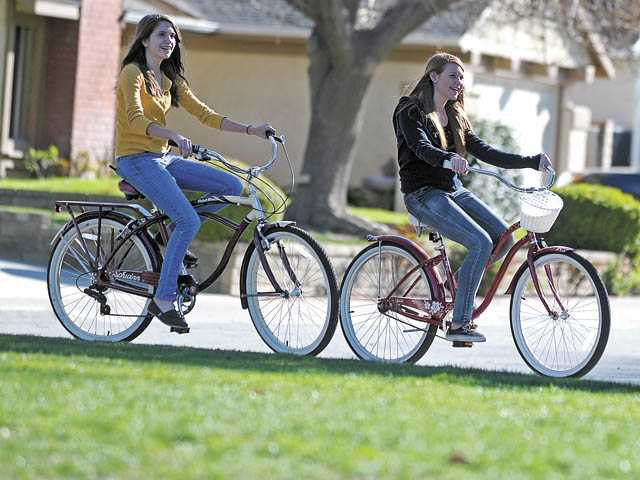 Paige Carlson, 14, left, and Sarah Morris, 13, ride their bicycles at Valencia Glen Park.