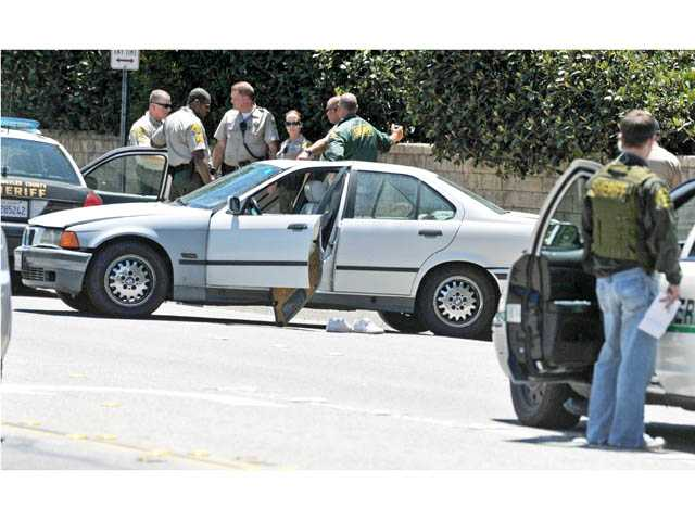 Sheriff's deputies investigate a traffic collision involving a BMW sedan on southbound Seco Canyon Road at Chapparo Drive in Saugus on Thursday.
