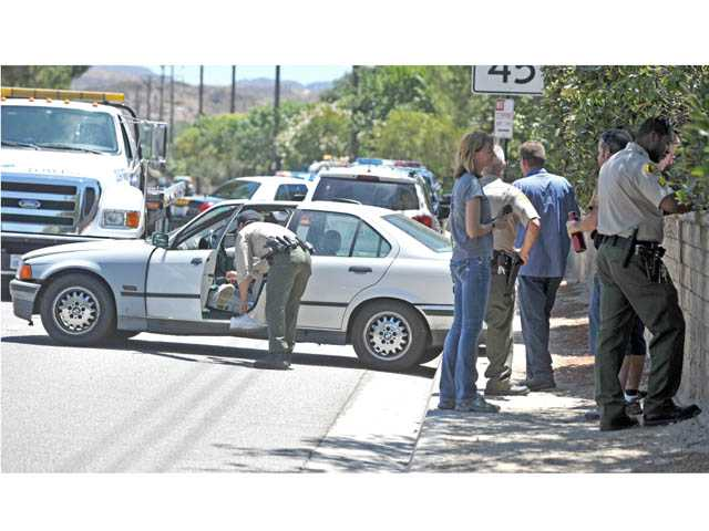 Sheriff's deputies investigate a traffic collision on southbound Seco Canyon Road at Chaparro Drive in Saugus on Thursday.
