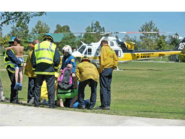 Paramedics and family members surround and care for a 3-year-old male victim of a near drowning before he taken to a helicopter at Valencia Heritage Park on Thursday.