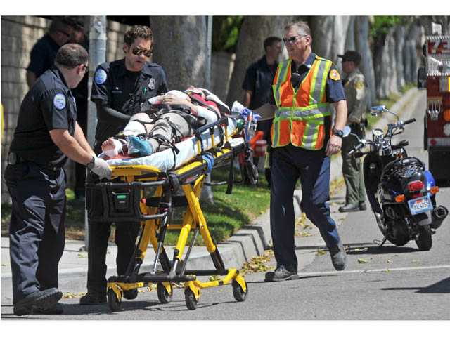 A woman is taken to an ambulance after a crash involving her scooter on Orchard Village Road at Dalbey Drive in Valencia on Thursday.