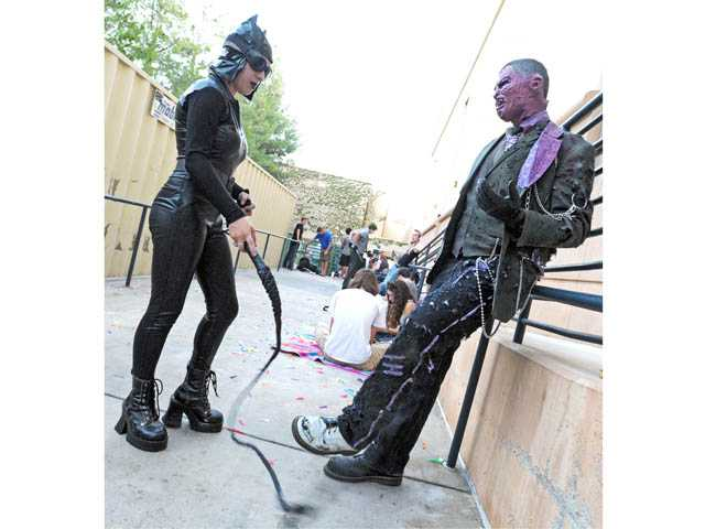 "Cait Davis, of Newhall, left, and Andrew Aguirre, of Canyon Country,  share a playful moment — portraying 'Batman' characters Catwoman and Two-Face respectively —as they await a screening of ""The Dark Knight Rises"" at the Edwards Valencia Stadium 12 cinemas on Thursday."