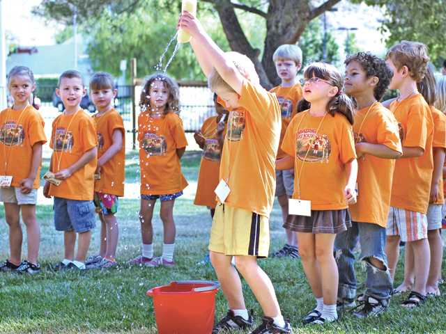 Vacation Bible school attendees play a water game at Bethlehem Lutheran Church.