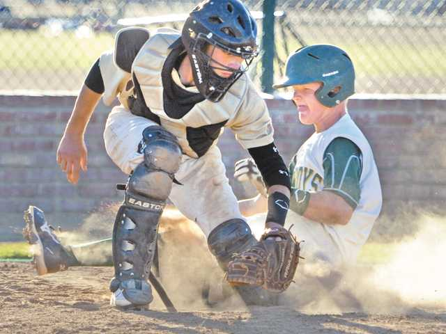 Canyon's Tyler Ryan, right, scores a run in the sixth inning as Kennedy catcher Chris Sandberg attempts to tag him out on Thursday at Canyon High School.