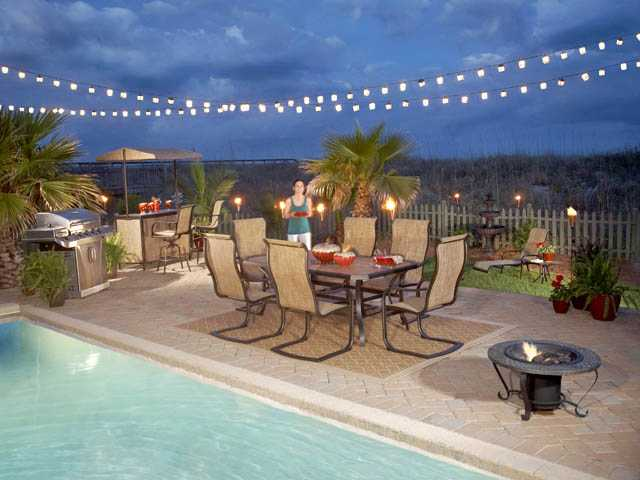 Your backyard patio can be a place of beautiful refuge and entertainment. This patio features a centerpiece outdoor dining set and firepit as well as barbecue, bar and fountain.