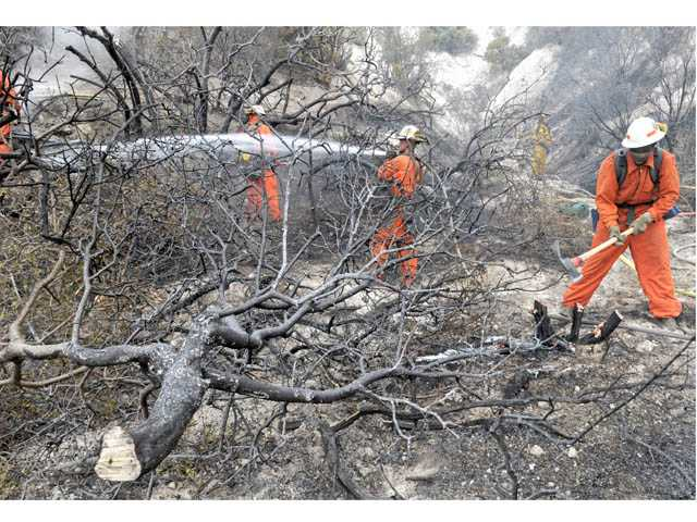 A hand crew clears brush after a fire burned near Soledad Canyon Road in Agua Dulce on Wednesday.