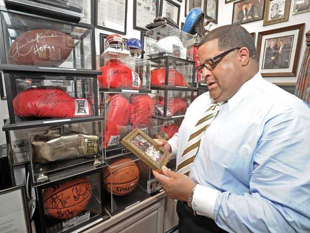 Perry displays a photo of Mohammed Ali signing a boxing glove in his collection of sports memorabilia at his home office. He is an avid fan of boxing.