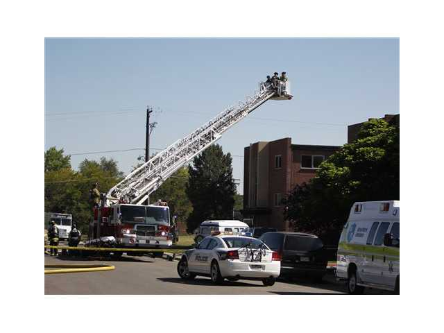 Police use the bucket on a fire truck to look down on an apartment where the suspect in a theatre shooting lived in Aurora, Colo., on Friday.
