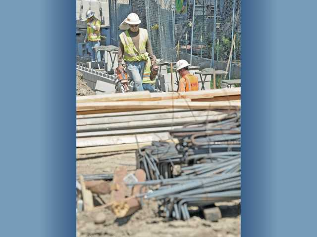 Workers build a block wall near piles of rebar at the site of the Regional Sports Complex Pool Project in Castaic on Friday.