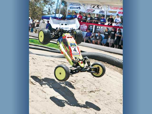 Drivers watch their cars from the drivers stand as one of their 1/10-scale model buggies go airborne during a qualifying race at the 15th annual Hot Rod Hobbies Off-Road Shootout RC race competition held at Hot Rod Hobbies in Saugus on Saturday.