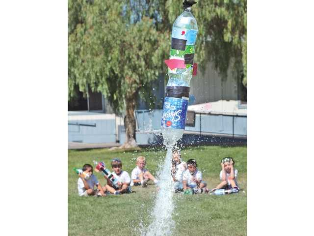 A group of first-graders watch a water-powered bottle rocket take off during a demonstration at Camp Invention, a science camp, at Agua Dulce Elementary School on Friday.