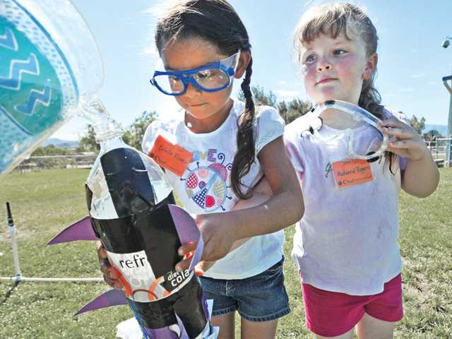 First-graders Brielle Flores, left, and Makenna Rogers fill the rocket they made from bottles with water at Agua Dulce Elementary School in Agua Dulce on Friday.