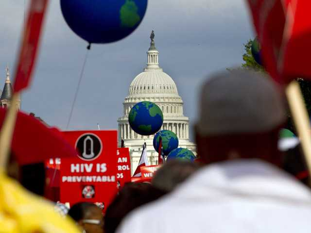 People hold signs and balloons as they participate in the AIDS March in Washington, on Sunday.