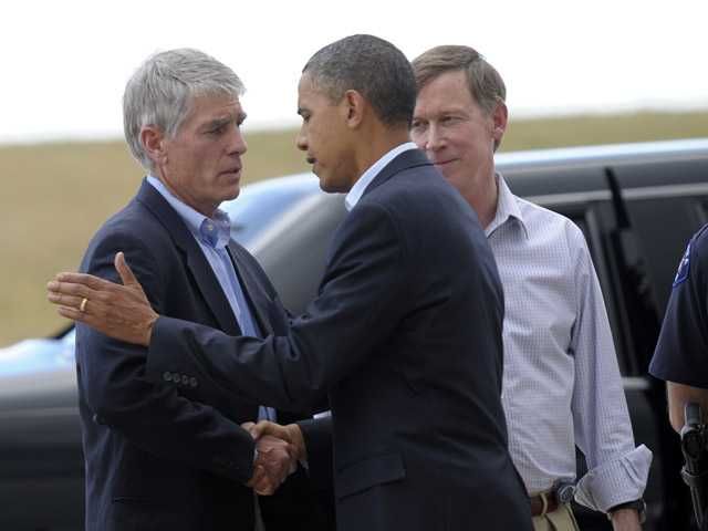 President Barack Obama, second from left, talks with Sen. Mark Udall, D-Colo., left, as Aurora, Colo., and right, watch, after Obama arrived at at Buckley Air Force Base, Colo., Sunday.