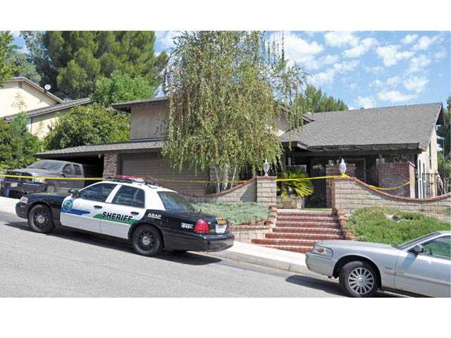 Crime scene tape surrounds a home on the 22900 block of Frisca Drive in Valencia on Monday.