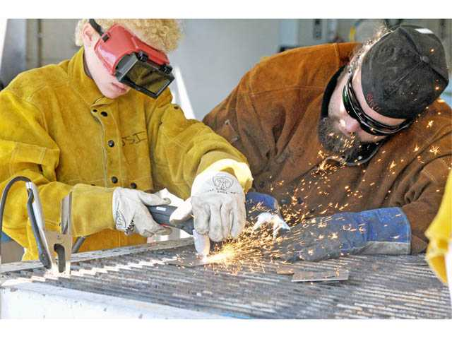 Pierce Monahan, 12, left, and lab technician Jared Schnitker use a plasma cutter in a welding class at College of the Canyons' Summer Institute in Valencia on Monday.
