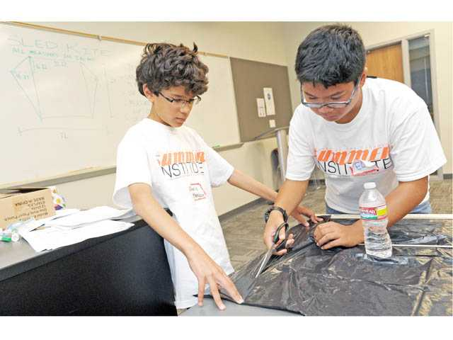 Chris Mendoza, 12, left, and Elijah Bulatao, 13, begin work on a sled kite in a NASA aeronautics class at College of the Canyons' Summer Institute in Valencia on Monday
