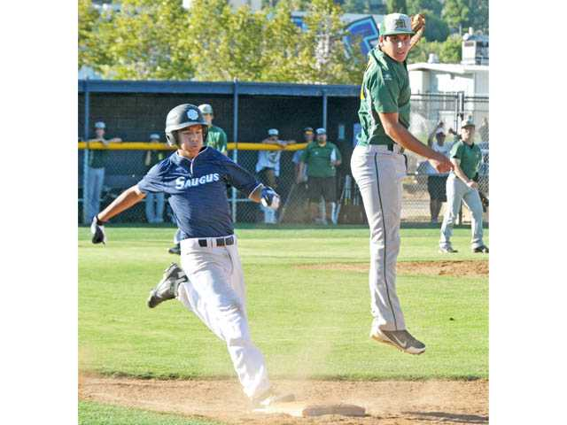 Moorpark's David Frank, right, is unable to catch the ball at first base as Saugus' Rudy Aguilar reaches the base during a game on Monday at Saugus High.