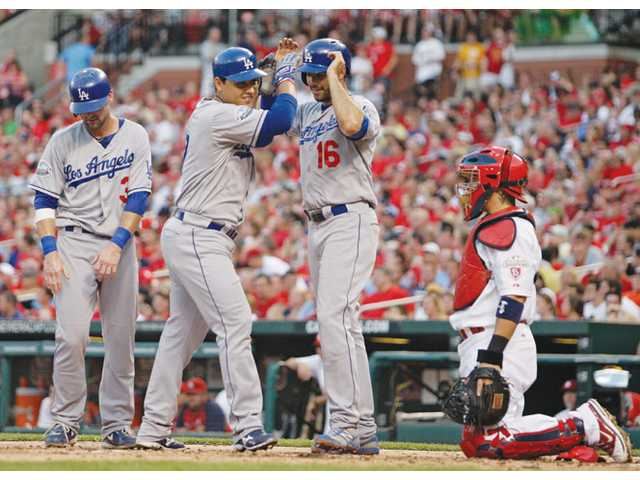 Los Angeles Dodger Luis Cruz, center, celebrates with teammates Andre Ethier (16) and Adam Kennedy (3), as St. Louis Cardinals catcher Yadier Molina looks on, after they all scored on Cruz's three-run home run on Monday in St. Louis.