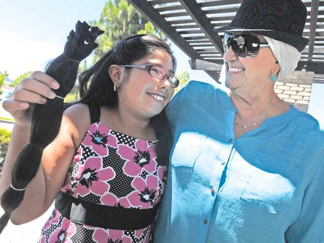 Fernanda Montoya, 10, left, of Canyon Country, holds locks of her hair that she cut on Tuesday to donate to cancer patients like Silvia Sachez, right, of Canyon Country who was diagnosed with lymphoma.
