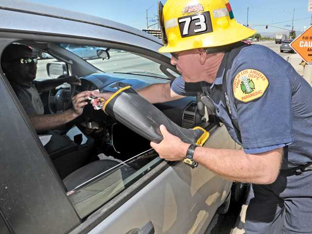 "A passing motorist receives a sticker after giving a donation to firefighter/paramedic Brian Ballentine of Fire Station 73 at the corner of Soledad Canyon Road and Bouquet Canyon Road during the ""Fill the Boot"" campain in Valencia on Tuesday."