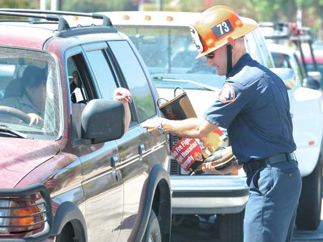 A passing motorist gives a donation to fire Captain Paul Peppard of Fire Station 73 at the corner of Soledad Canyon Road and Bouquet Canyon Road during the Fill the Boot campaign in Valencia on Tuesday. The campaing will continue today and Thursday.