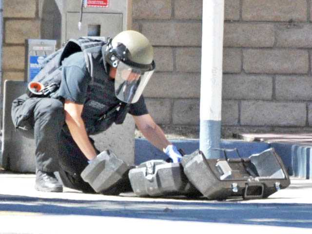 A sheriff's station bomb squad investigator examines the contents of a suspicious package found at the Shell gas station at Valencia Boulevard at McBean Parkway in Valencia on Wednesday.