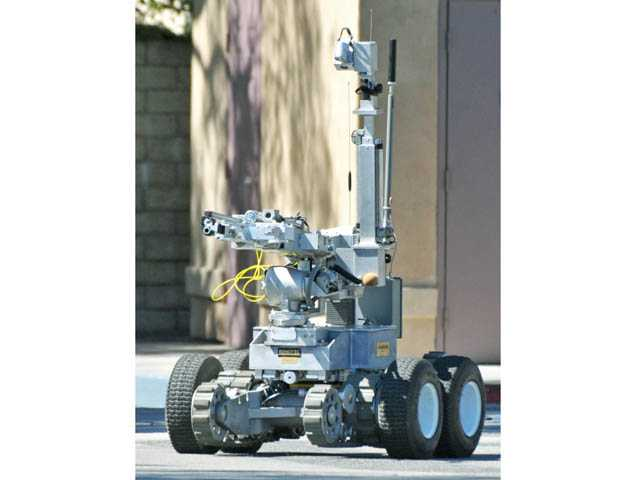 A remote-controlled robot leaves the scene after it approached and examined a suspicious package found at the Shell gas station at Valencia Boulevard and McBean Parkway in Valencia on Wednesday.