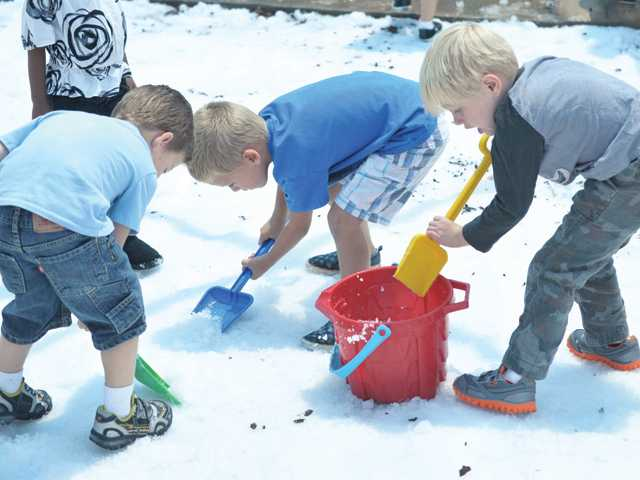 "A group of kindergartners shout ""Let's make ice cream"" as they shovel snow into a bucket during the snow day event at Creative Years Preschool in Santa Clarita on Wednesday."
