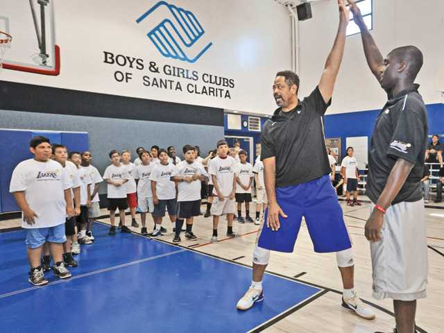 Daryl Roper, Lakers Youth Foundation organizer, center, and coach Mike Ojo demonstrate a move for attendees of the Lakers Youth basketball clinic held at the Boys & Girls Club in Newhall on Thursday.
