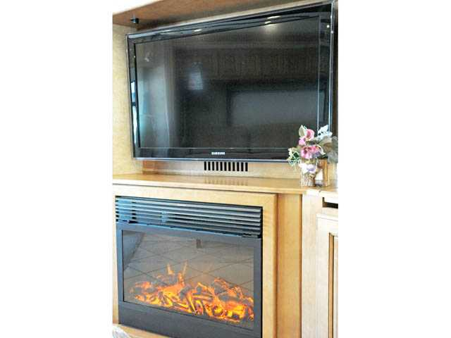 A flat-panel television and a fireplace aboard a 2012 Itasca Meridian motorhome. New RVs offer a wealth of features and home comfort.